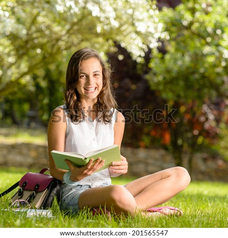 Cheerful girl with open book sitting on grass summer park