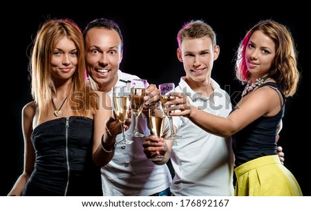 Cheerful group of young people with glasses of sparkling champagne over black background