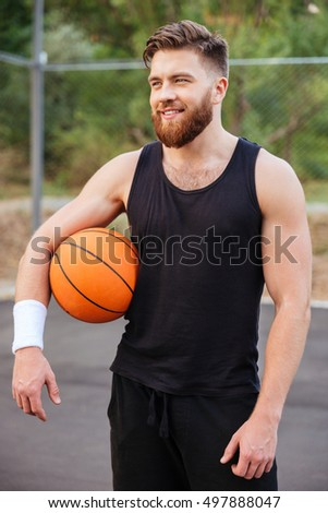 Cheerful happy basketball player standing with ball outdoors