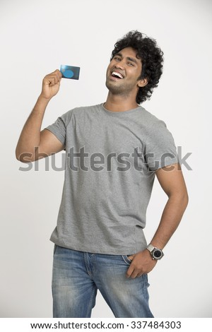 Cheerful happy Indian young man showing credit card on white.