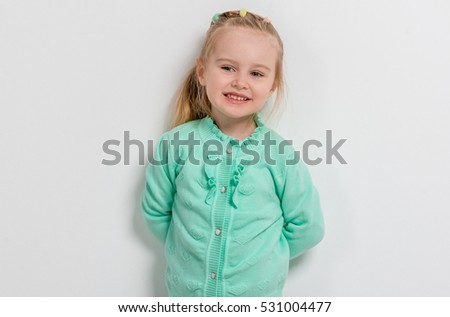 cheerful little girl in turquoise sweater with