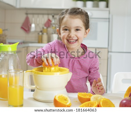 Cheerful little girl making her self an orange juice