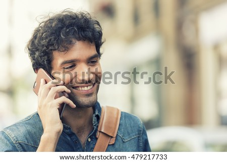 Cheerful male in the street on Mobile phone.