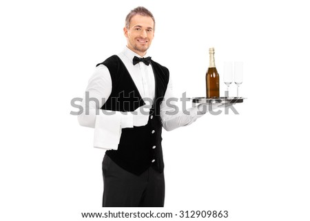 Cheerful male waiter with a bow-tie and black vest holding a tray with a champagne and two empty glasses on it isolated on white background