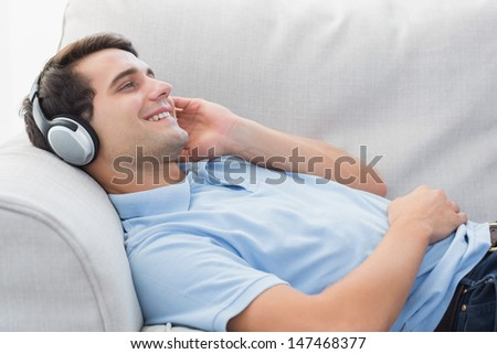 Cheerful man enjoying music lying on a couch in the living room