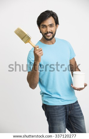 Cheerful man holding a paint brush and a paint bucket, looking at camera