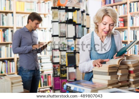 Cheerful mature woman looking at open book in hands in book shop