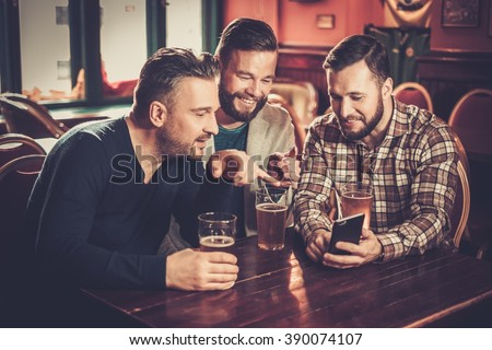 Cheerful old friends having fun with smartphone and drinking draft beer in pub.