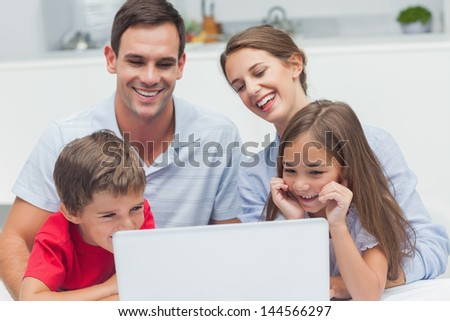 Cheerful parents and children using a laptop in the kitchen