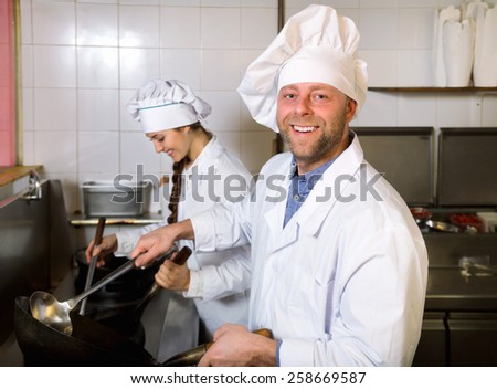 Cheerful professional chef and cook  working at take-away restaurant kitchen