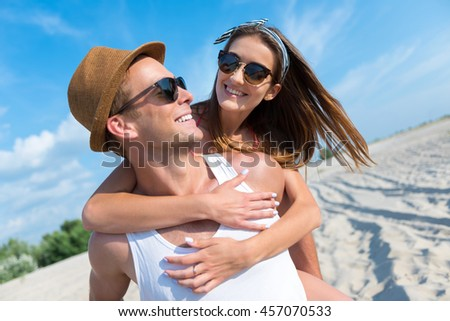 Cheerful smiling couple resting on the beach