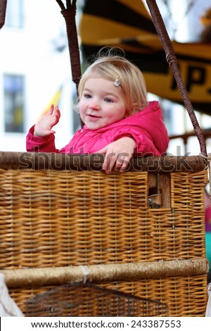 Cheerful smiling little child, toddler girl wearing warm pink coat, having fun riding on the merry-go-round during funfair entertainment