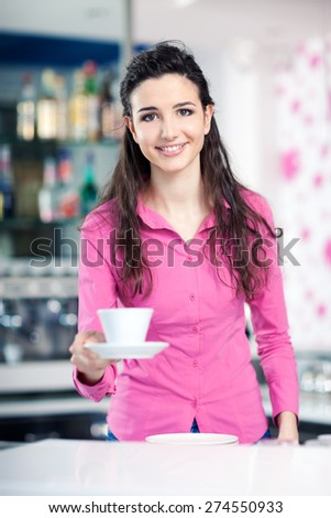 Cheerful smiling waitress in a coffee shop serving an hot espresso