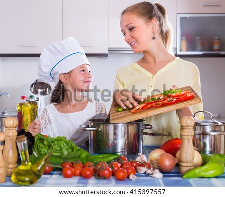 Cheerful smiling woman and her daughter with veggies at kitchen table