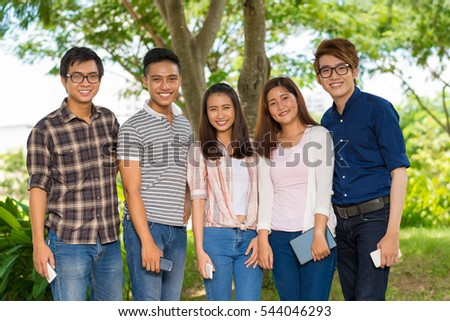 Cheerful students looking at camera when standing outdoors