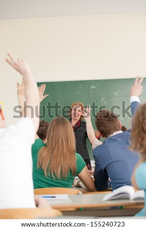 Cheerful teacher in a classroom looking at asking students