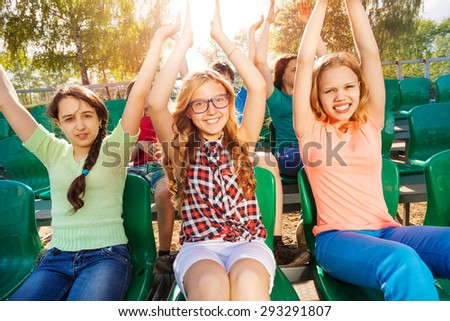 Cheerful teenagers hold arms up during game