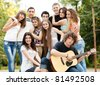 Cheerful teenagers playing guitar and singing - stock photo