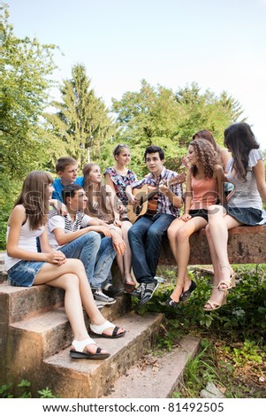 Cheerful teenagers playing guitar and singing