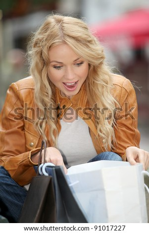 Cheerful woman looking at shopping bags