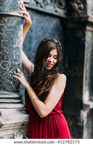 Cheerful young brunette in a red dress posing with old Lviv cathedral on background