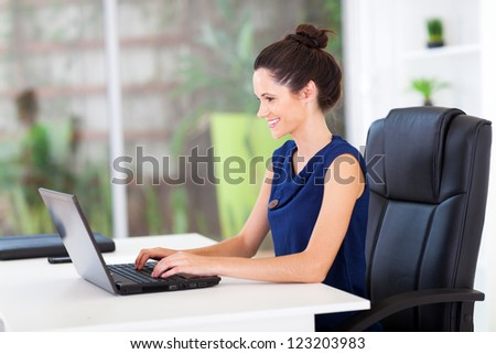 cheerful young businesswoman working in office