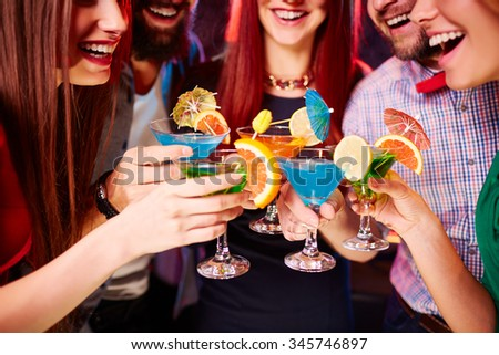 Cheerful young friends toasting with cocktails