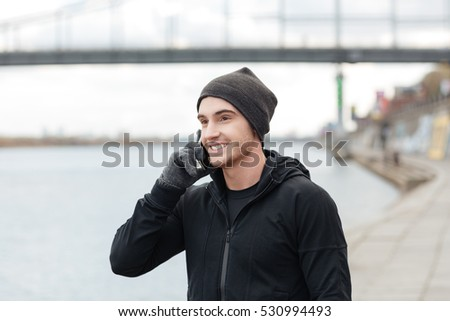 Cheerful young man in hat and gloves talking on mobile phone outdoors