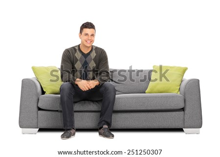 Cheerful young man sitting on a modern sofa isolated on white background