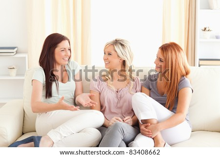 Cheering friends sitting on a sofa in a living room