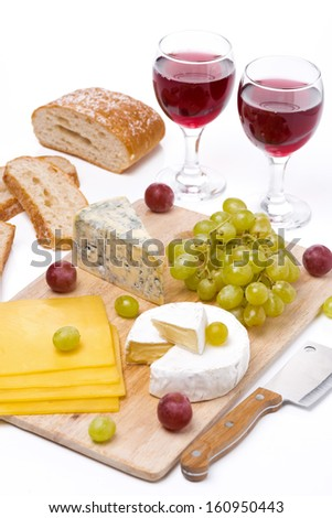 Cheese platter, grapes, bread and red wine on a wooden board, vertical