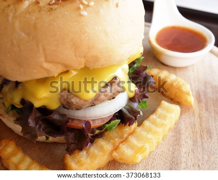 cheeseburger with fries  served on plate at restaurant