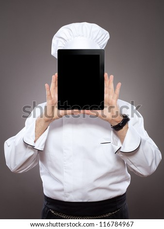 Chef behind the digital tablet against grey background