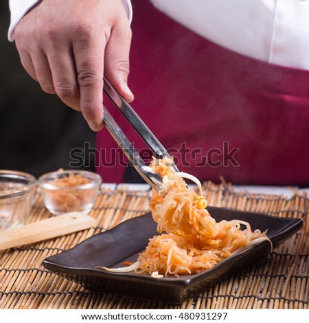 Chef fork over noodles by tongs / cooking Pad Thai concept