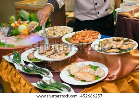 chef preparing plates of various meat, pork, beef, chicken, fish, shrimp and squid for dinner in a luxury restaurant.