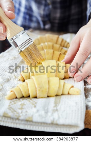 Chef smearing raw croissants with brush in yolk, preparation process. Dough for croissant sweet traditional dessert.