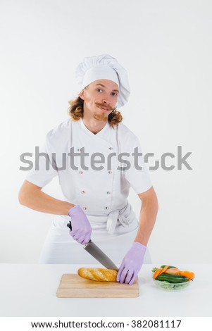 Chef with in white uniform slice the bread and smile, vegetable salad is on the table in front of him. Conception of healthy food and healthy lifestyle. Cooking vegetarian sandwich
