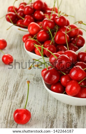 Cherry berries in bowl on wooden table close up