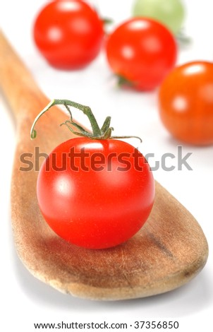 Cherry tomato and spoon with some more in a background
