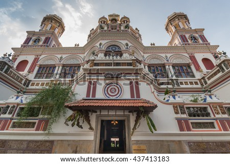 Chettinad, India - October 17, 2013: Chidambara Palace in Kadiapatti. Front view on facade shows towers, balconies, balustrades, the front entrance, Krishna decorations. Mainly beige and purples