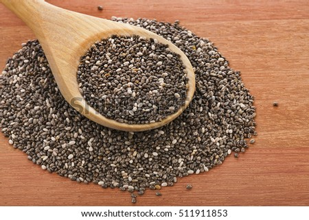 Chia seeds in a wooden spoon on a wooden table, top view