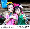 CHIANG RAI,THAILAND-AUGUST 25: Unidentified Karen tribe girls pose for the camera in Chiang Rai on August 25, 2012.The Karen people wear brass rings around their neck from as young as five years old. - stock photo