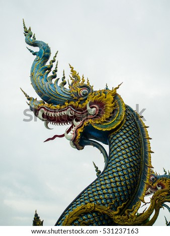 Chiang Rai, Thailand : November 27, 2016 , The fierce face naga sculpture at Rong Suea Ten Temple, the temple which is decorate in blue tone color, Chiang Rai, Thailand