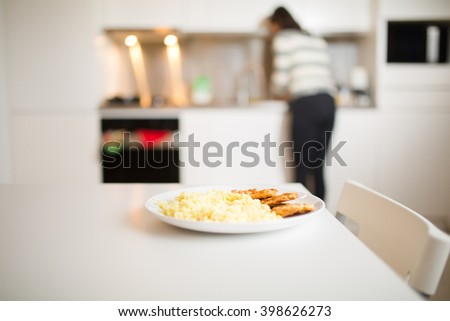 Chicken and rice on a plate,healthy nutrition fitness diet food and woman in the background cooking at home.Eating in.Cooking healthy delicious meal at home.Single person cooking dinner for one alone