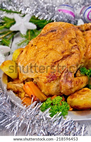 Chicken baked with vegetables and apples on a metal plate, silver toys, fir branches on the background of wooden boards