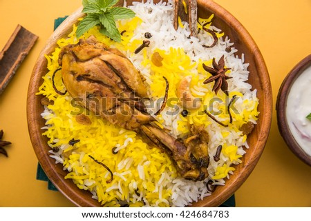 Chicken Biryani with yogurt dip on beautiful moody background, selective focus