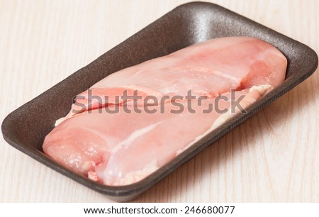 Chicken breast fillets in black food packaging tray