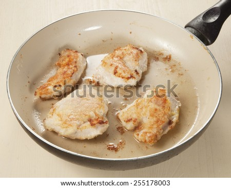 Chicken breast on a frying pan with oil