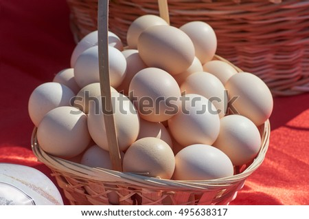 Chicken eggs in a wicker basket on red outdoor