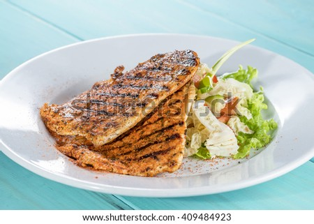 chicken grilled with fresh salad mix on the painted wooden background